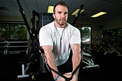Strong Man Working Out. A strong, handsome man lifting weights in a gym Stock Photography