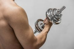 Strong man working out with dumbbell stock images
