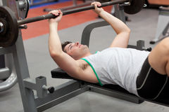 Strong man working out with dumbbells. In a fitness center Stock Image