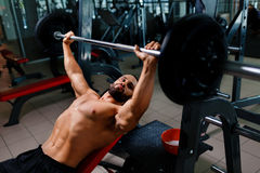 A strong man working out exercises with a barbell on a gym background. An athletic guy keeps barbell plate in hands. stock images