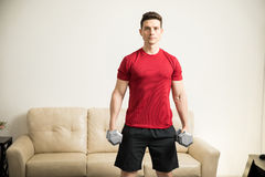 Strong man working out at home Royalty Free Stock Photo