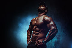 Strong man. Young strong man bodybuilder in cap on wall background. Dark dramatic colors Royalty Free Stock Images