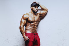 Strong man. Young strong man bodybuilder in cap on white wall background Royalty Free Stock Image