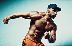 Strong man. Young strong man bodybuilder in cap on stone wall background royalty free stock photo