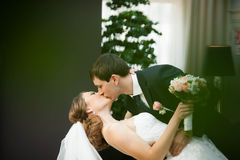 Strong manly groom kisses his bride Stock Images