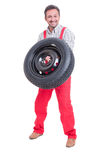 Strong mechanic lifting car wheel with tire Stock Image