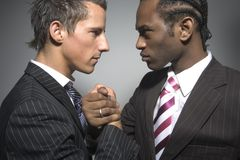 Strong men. Two suited businessmen faceing each other stock photos