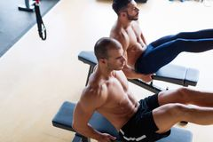 Strong men are doing abs crunches on bench Stock Image