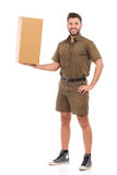 Strong messenger. Happy delivery man standing and holding big package in one hand. Full length studio shot isolated on white Royalty Free Stock Image