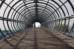 Metal tunnel bridge with wooden walkway Royalty Free Stock Photography