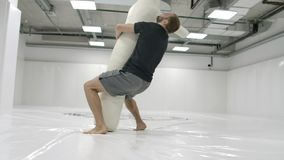 A strong mma fighter is training to throw a scarecrow. Testing wrestling equipment.  stock video