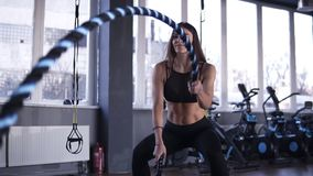 Strong, motivated, positive woman battling ropes in gym during cross-training workout. Slow motion stock footage