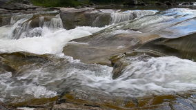 Strong mountain stream flowing over rocks stock footage