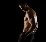 Strong muscular athlete posing on black Stock Images