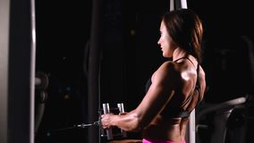 A strong, muscular, athletic bodybuilder girl, in short shorts, trains the back muscles on a horizontal simulator in a. Dark gym stock video