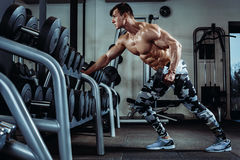 Strong muscular bodybuilder doing exercise in the gym. Part of fitness body. Royalty Free Stock Image