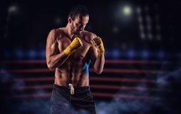 Strong muscular boxer in red boxing gloves. A man in a boxing Stock Images