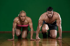 Strong Muscular Couple Kneeling On The Floor stock photography
