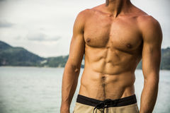 Strong muscular fit man posing in a swimsuit. On a tropical beach showing off his powerful physique, anonymous torso view Stock Images