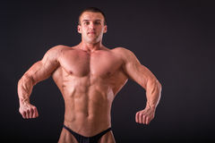Strong, muscular guy on a black background. Man posing, man straining muscles. Muscles of the arms, torso, abdominal muscles stock photo