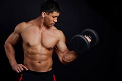 Strong muscular guy is training with dumbbel at gym. Close up side view photo. interest, lifestyle concept stock images