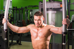 Strong muscular handsome man exercising at the gym Stock Photos