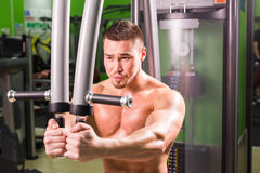Strong muscular handsome man exercising at the gym Stock Photo