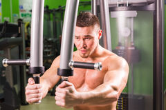 Strong muscular handsome man exercising at the gym Stock Images