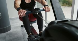 Strong Muscular male working on indoor rower simulator. Cross Fitness Training in the gym.  stock video