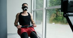 Strong Muscular male working on indoor rower simulator. Cross Fitness Training in the gym.  stock video footage