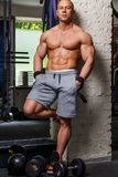 Strong muscular man. Bodybuilder poses and shows his trunk Stock Image