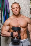Strong muscular man. Bodybuilder shows his muscles holding dumbbells Stock Image