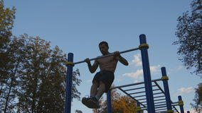 Strong muscular man doing muscle ups in a park. Young athlete doing chin-ups on horizontal bars outdoor. Fitness stock video footage
