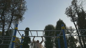 Strong muscular man doing muscle ups in a park. Young athlete doing chin-ups on horizontal bars outdoor. Fitness. Muscular man training outside in summer stock video