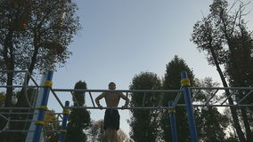 Strong muscular man doing muscle ups in a park. Young athlete doing chin-ups on horizontal bars outdoor. Fitness. Muscular man training outside in summer stock footage