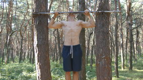 Strong muscular man doing pull ups in a forest. Young athlete doing chin-ups on horizontal bars at the wood. Fitness. Muscular man training outdoor in summer stock video