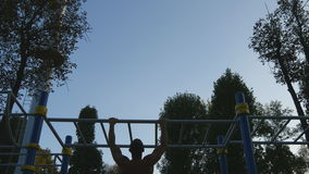Strong muscular man doing pull ups in a park. Young athlete doing chin-ups on horizontal bars outdoor. Silhouette of. Fitness muscular man training outside in stock video