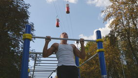Strong muscular man doing pull ups in a park. Young athlete doing chin-ups and performs exercises on horizontal bars. Outdoor. Fitness muscular man training stock video footage