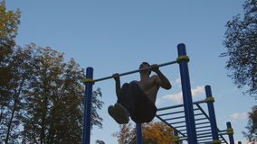 Strong muscular man doing pull ups in a park. Young athlete doing chin-ups and performs exercises on horizontal bars stock video