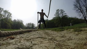 Strong muscular man exercising with ropes stock footage