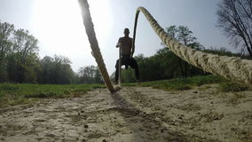 Strong muscular man exercising with ropes stock video