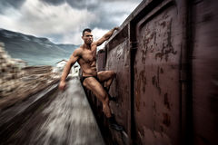 Strong muscular man holding on moving train Royalty Free Stock Photos