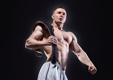 Strong muscular man with lifting belt posing over stock photography
