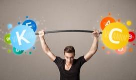 Muscular man lifting colorful vitamin weights. Strong muscular man lifting colorful vitamin weights royalty free stock image