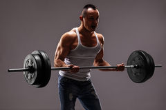 Strong muscular man lifting a heavy barbell Stock Image