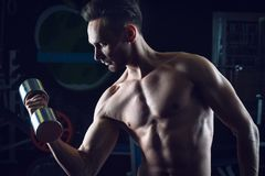 Strong Muscular man with naked torso abs working out in gym doing exercises with dumbell at biceps.  Stock Images