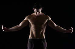 Strong muscular man posing on black Stock Photo