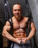 Strong muscular man. Bodybuilder poses and shows his abs and bicepses Stock Photography