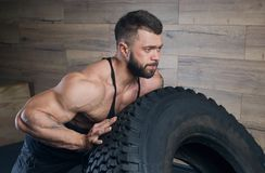 Strong muscular man with tattoos and beard pushing a tire in a black tank top and grey shorts in the gym royalty free stock photos