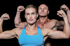 Strong muscular man and woman flexing muscles. Strong muscular men and women flexing muscles against black background royalty free stock photos